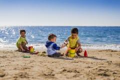 使用与海滩玩具的小组孩子 免版税库存照片