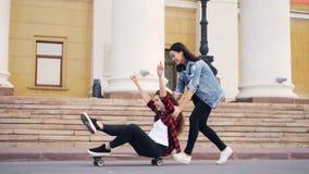 使用与滑板的激动的女孩的慢动作坐longboard和推挤它笑和获得乐趣 股票视频