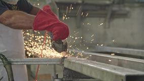 使用与火花的工作者的慢动作金属研磨机飞行在金属商店 影视素材