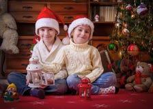 使用与灯笼的两个孩子在圣诞树下 免版税库存照片