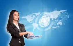 使用与焕发的妇女数字式片剂和世界地图 库存图片