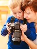 使用与照相机的母亲和孩子拍照片 免版税库存图片