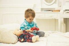 使用与熊的小男孩 幸福家庭和儿童节 儿童游戏玩具 愉快的童年 关心和发展 库存图片