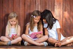 使用与片剂和巧妙的电话的三个女孩。 图库摄影