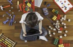 使用与片剂计算机的小男孩 全部在他附近的玩具在木地板上 顶视图 图库摄影
