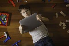 使用与片剂计算机的小男孩 说谎在地板,在他附近的许多玩具上的孩子在木地板上 库存照片