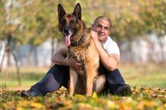 使用与狗德国牧羊犬的人在公园 库存图片