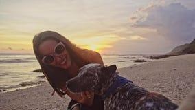 使用与狗的太阳镜的年轻无忧无虑的妇女,抚摸a和在海滩的亲吻狗在惊人的日落期间 一好 影视素材