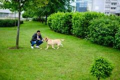 使用与狗的男人和妇女在公园 免版税图库摄影