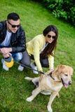 使用与狗的男人和妇女在公园 免版税库存图片