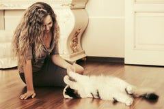 使用与猫的美丽的妇女在公寓 免版税库存照片
