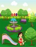 使用与猫的逗人喜爱的小女孩在公园 免版税库存图片