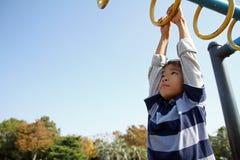使用与猴子栏杆的日本男孩 免版税库存图片