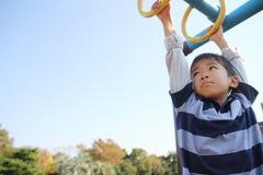 使用与猴子栏杆的日本男孩 免版税图库摄影