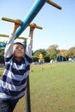 使用与猴子栏杆的日本男孩 库存图片