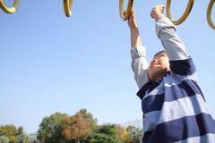 使用与猴子栏杆的日本男孩 免版税库存照片