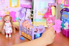 使用与玩偶的小女孩 女孩在她的手上的拿着一个玩偶 逗人喜爱的玩偶和玩具家具在桌上 滑稽的比赛 库存图片