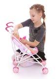 使用与玩偶的逗人喜爱的小女孩,在婴儿推车投入她 库存图片