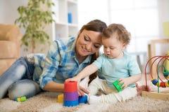 使用与玩具一起的孩子和他的母亲 免版税库存照片
