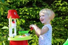 使用与玩具厨房的小女孩户外 免版税库存照片