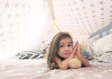 使用与玩具和作梦在圆锥形帐蓬和床的逗人喜爱的愉快的小女孩 关闭愉快的孩子照片  库存照片