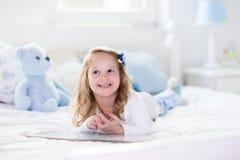 使用与玩具和在床上的小女孩读一本书 免版税库存图片