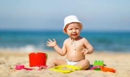 使用与玩具和沙子的男婴在海滩 库存图片