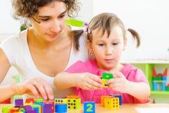 年轻使用与玩具块的母亲和小女儿 免版税库存照片
