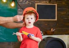 使用与玩具工具的激动的孩子 呼喊在车间的白肤金发的男孩 Daddys小的帮手 拿着桔子的男性手 库存图片
