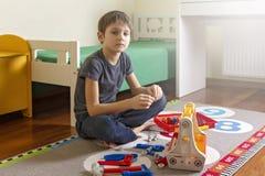 使用与玩具工具箱的男孩,当坐地板在他的屋子里时 免版税库存图片