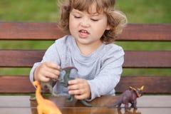 使用与玩具恐龙的小孩孩子户外 免版税库存图片
