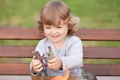使用与玩具恐龙的小孩孩子户外 图库摄影