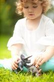 使用与玩具恐龙的小孩孩子 免版税库存照片