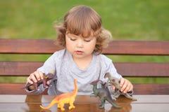 使用与玩具恐龙的小孩孩子 库存图片