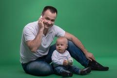 使用与玩具手机的父亲和小孩儿子 免版税库存照片