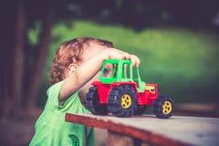 使用与玩具拖拉机的逗人喜爱的孩子 库存图片