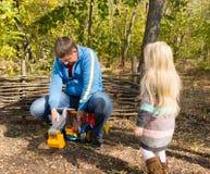 使用与玩具挖掘机的父亲和女儿 免版税库存照片