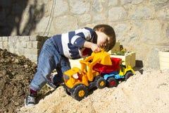 使用与玩具挖掘者和倾销者卡车的小男孩 免版税库存照片