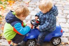 使用与玩具汽车的两个小兄弟姐妹孩子在秋天天 图库摄影