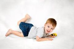 使用与玩具汽车的激动,年轻男孩 免版税库存照片