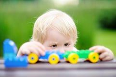 使用与玩具火车的小孩男孩户外 图库摄影