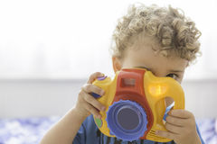 使用与玩具照片照相机的孩子 免版税库存图片