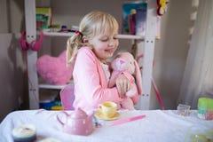 使用与玩具熊和玩具厨房集合的微笑的女孩 库存照片