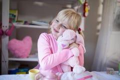 使用与玩具熊和玩具厨房集合的微笑的女孩 库存图片