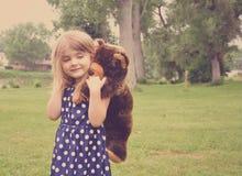 使用与玩具熊朋友的小女孩在公园 免版税图库摄影