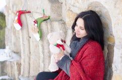 使用与玩具熊的一个美丽的微笑的女孩的画象在冬天 库存照片