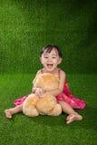 使用与玩具熊的亚裔矮小的中国女孩 免版税库存照片