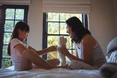 使用与玩具熊的女儿和母亲在床屋子里 免版税库存图片