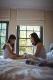 使用与玩具熊的女儿和母亲在床屋子里 库存图片