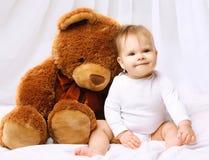 使用与玩具熊的微笑的婴孩 免版税库存图片